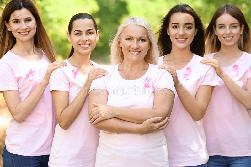 Beautiful women of different ages with pink ribbons outdoors. Breast cancer concept royalty free stock photography