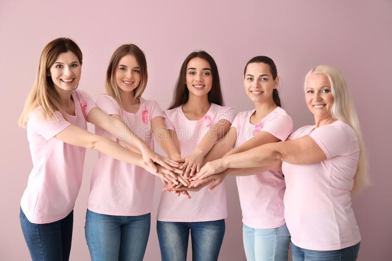 Beautiful women of different ages with pink ribbons putting hands together on color background. Breast cancer concept stock photos