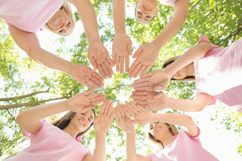 Beautiful women of different ages with pink ribbons putting hands together outdoors. Breast cancer concept stock image