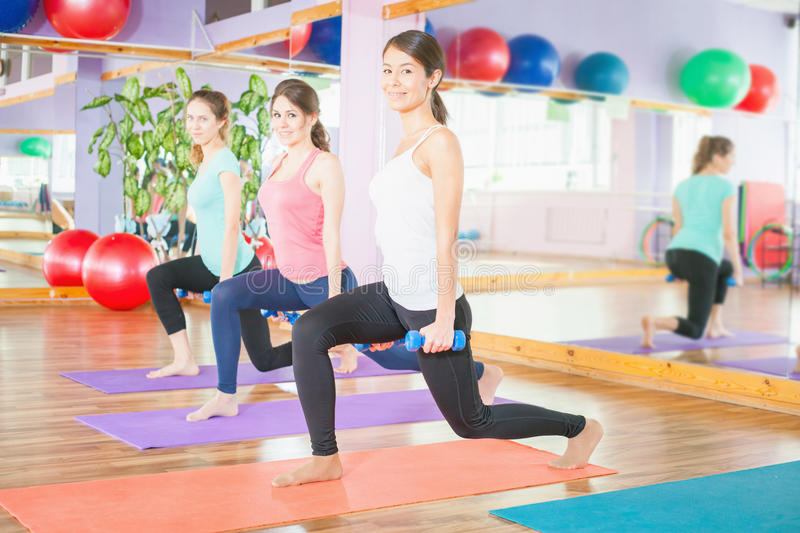 Beautiful women doing fitness exercise with weight in hands. Women doing squats, leg muscles pump up for buttocks royalty free stock photo