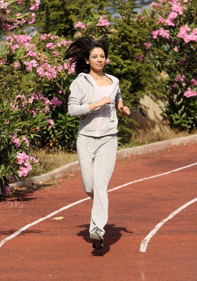 Beautiful women doing sports on the tartan track royalty free stock photography