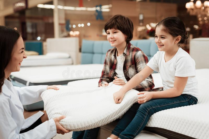 Beautiful woman dressed in white robe shows orthopedic pillow to young children sitting on mattress. Beautiful women dressed in white robe shows orthopedic stock photos