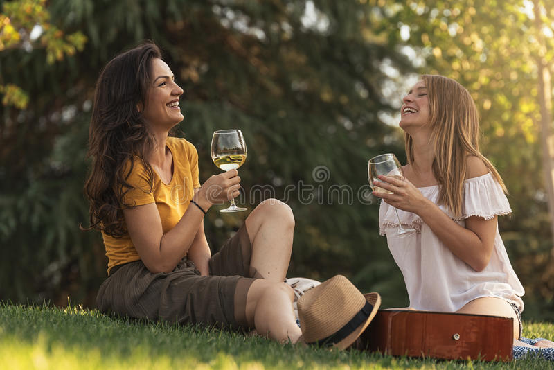 Beautiful women drinking wine in the park. stock photography