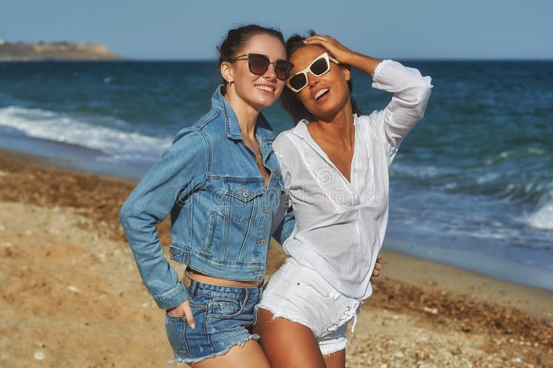 Beautiful women friends enjoy a walk on the beach on a Sunny day. Young beautiful women on vacation at the seaside . Girl friends enjoy a walk on the beach on a royalty free stock images