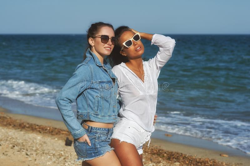 Beautiful women friends enjoy a walk on the beach on a Sunny day. Young beautiful women on vacation at the seaside . Girl friends enjoy a walk on the beach on a royalty free stock photos