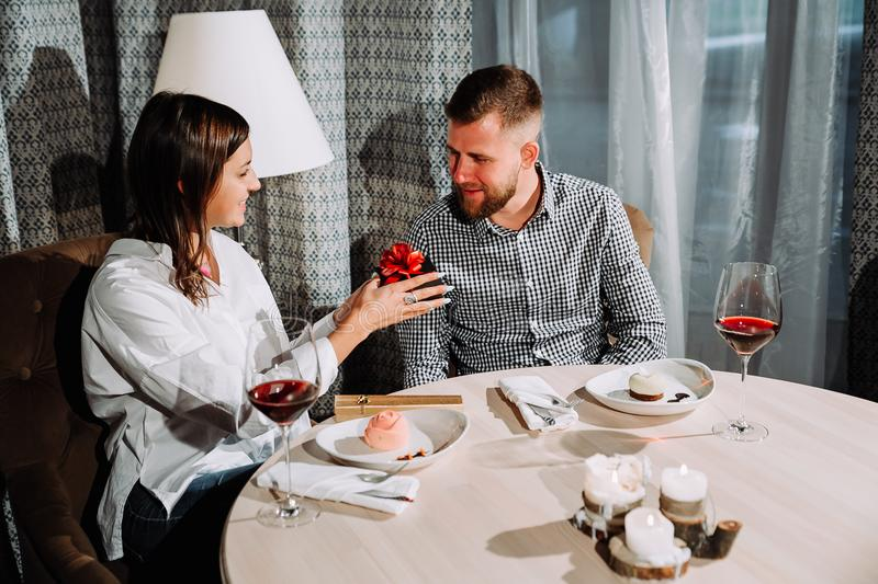 A beautiful brunette gives a gift to her boyfriend in a restaurant on a date royalty free stock photography