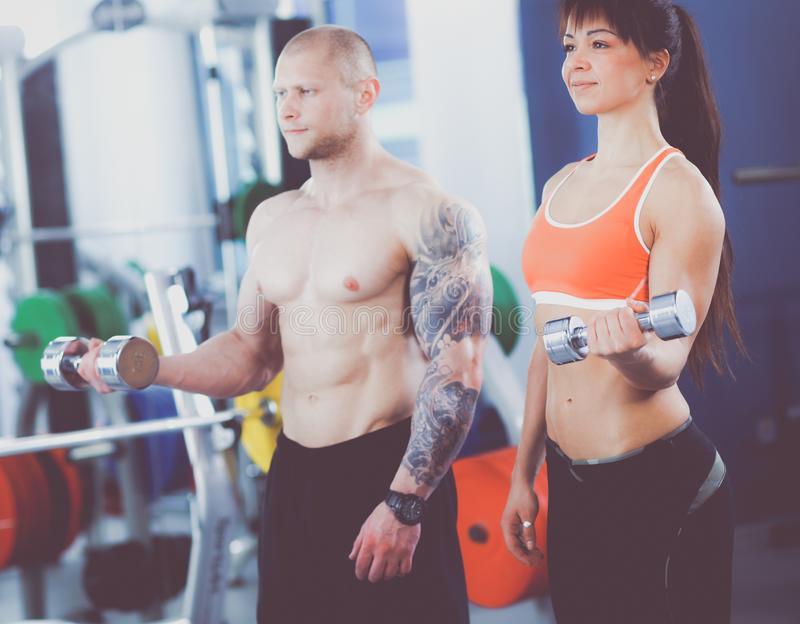 Beautiful woman at the gym exercising with her trainer . Beautiful woman. stock photo