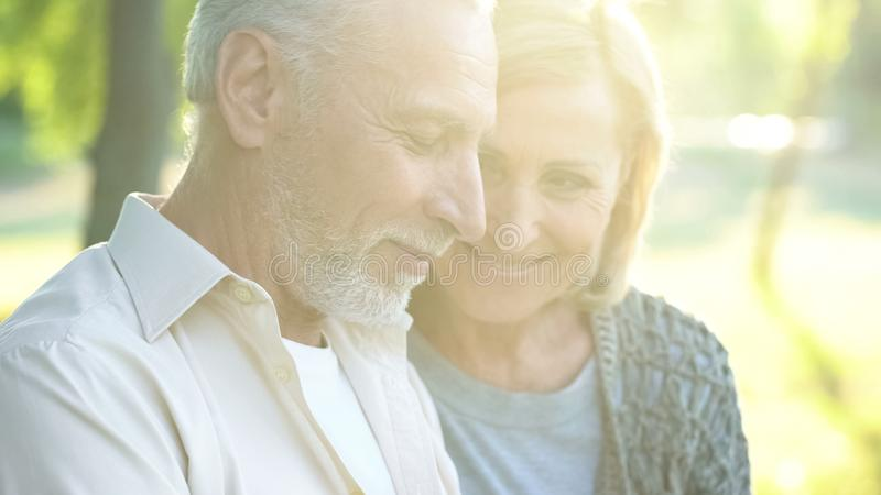 Beautiful woman in his 60s tenderly looking at retired male, happy aged couple royalty free stock photo