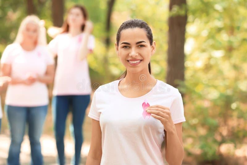 Beautiful woman holding pink ribbon outdoors. Breast cancer concept. Beautiful women holding pink ribbon outdoors. Breast cancer concept royalty free stock photo