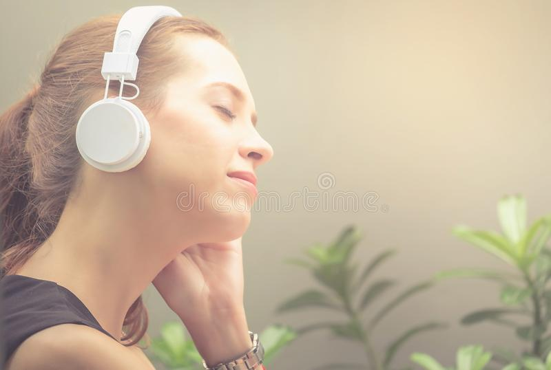 Beautiful women are listening to music with their eyes closed, a stock photo