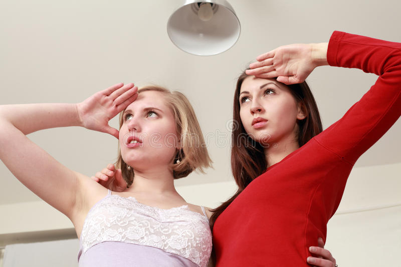 Beautiful women looking ahead. Two beautiful women looking ahead or afar shielding eyes with hands royalty free stock image