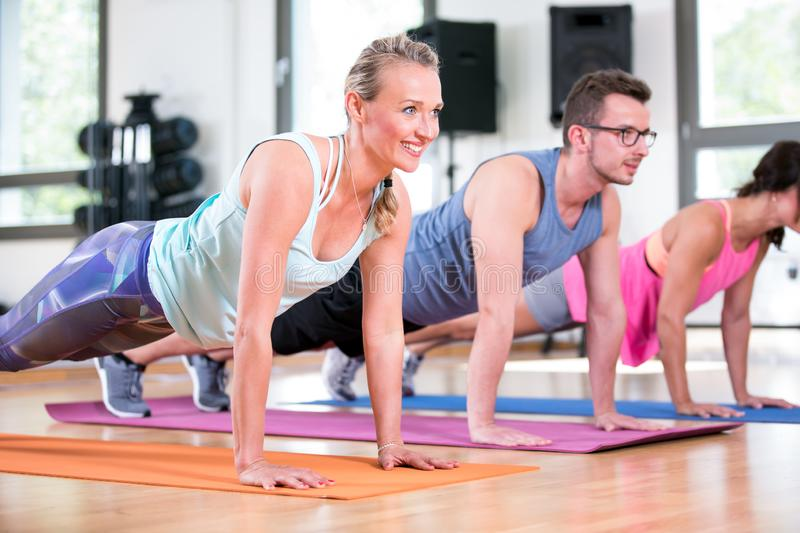 Beautiful women man group are doing sport fitness workout in a gym stock photography