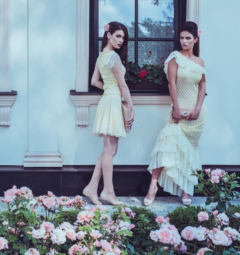Beautiful women near luxury building facade. Tow women in dress near luxury building facade among roses royalty free stock photos