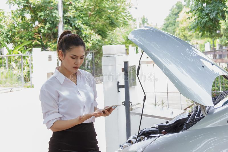 Beautiful women open radiator bonnet and holding smart phone for call service check. Beautiful woman open radiator bonnet and holding smart phone for call stock photo