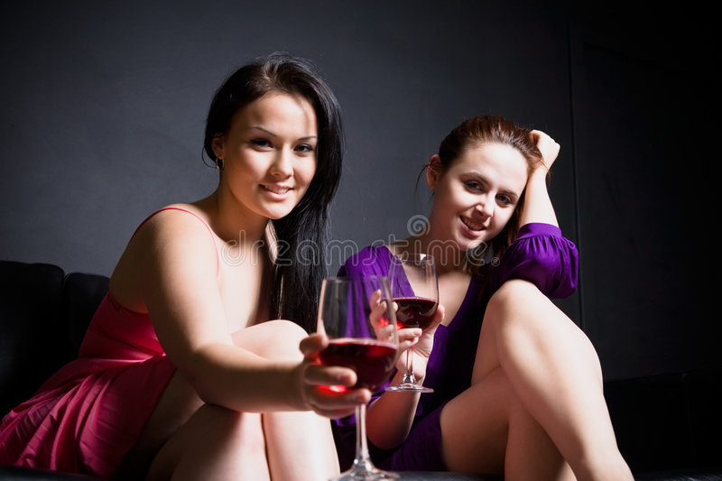 Beautiful women party time. Two beautiful women toasting their red wineglasses during the party royalty free stock image