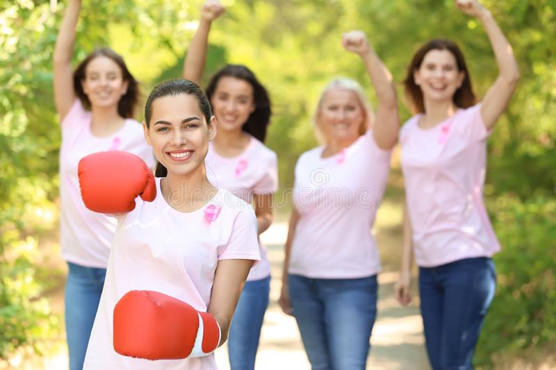 Beautiful woman with pink ribbon and boxing gloves outdoors. Breast cancer concept. Beautiful women with pink ribbon and boxing gloves outdoors. Breast cancer royalty free stock photography