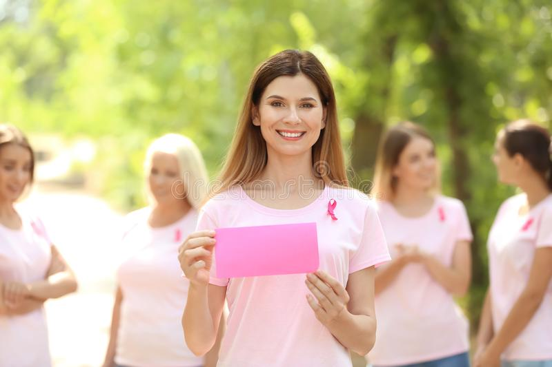 Beautiful woman with pink ribbon holding card outdoors. Breast cancer concept. Beautiful women with pink ribbon holding card outdoors. Breast cancer concept stock photos