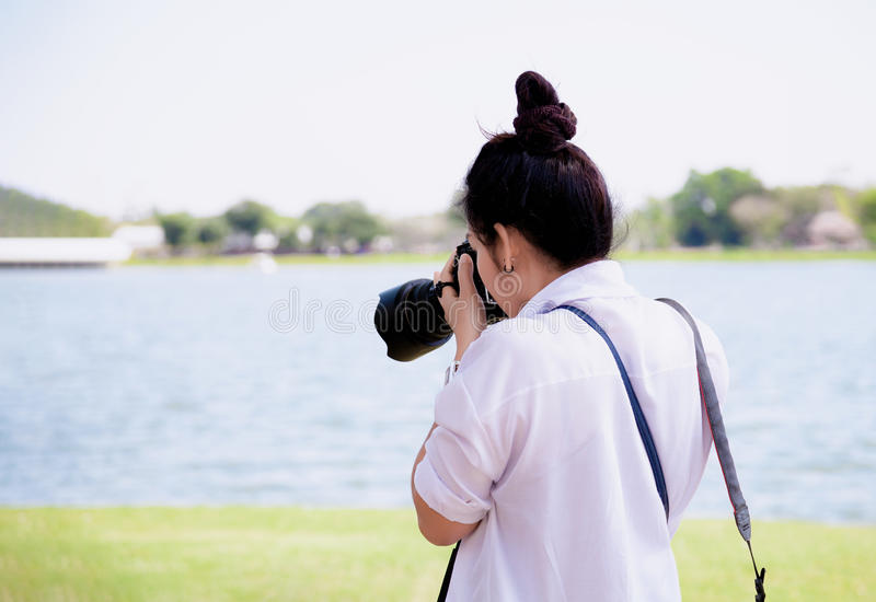 Beautiful women professional photographer takes images with DSLR camera., In the park. stock photo