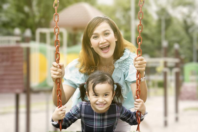 Beautiful woman pushes her child on the swing. Beautiful women pushing her child on the swing while playing in the playground stock images