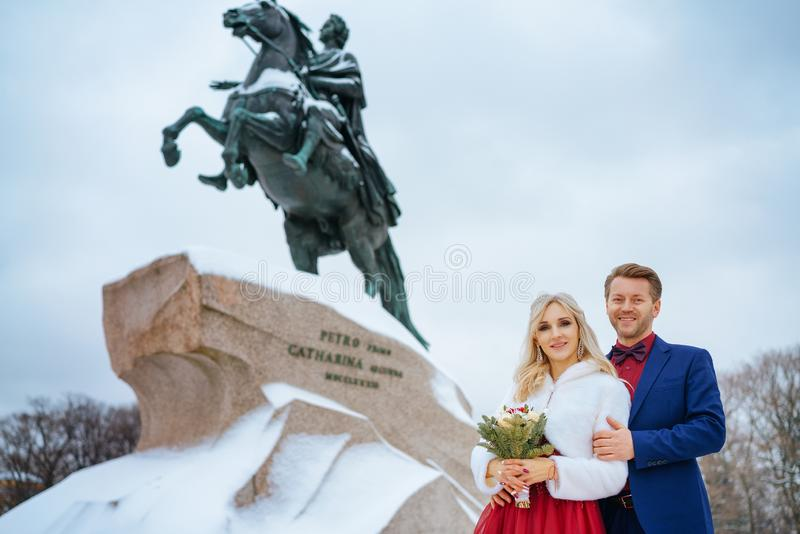 Beautiful woman in red dress and man posing standing in winter, wedding in St. Petersburg royalty free stock photo