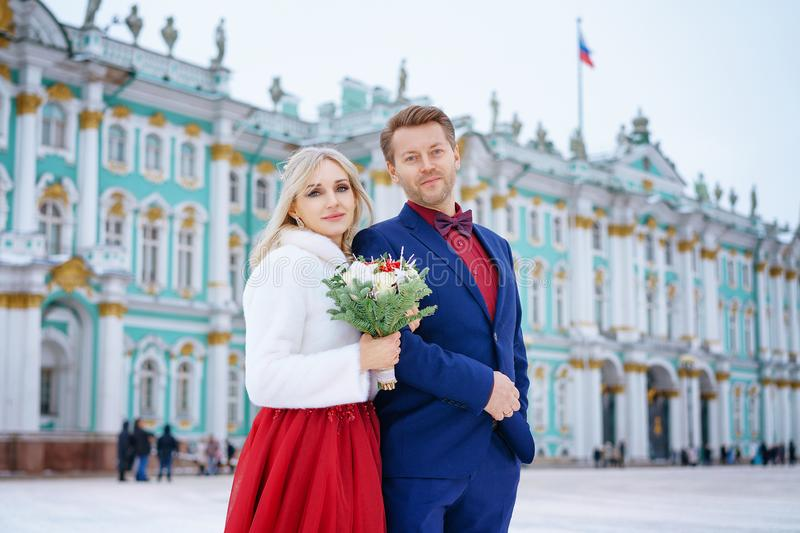 Beautiful woman in red dress and man posing standing in winter, wedding in St. Petersburg royalty free stock photos