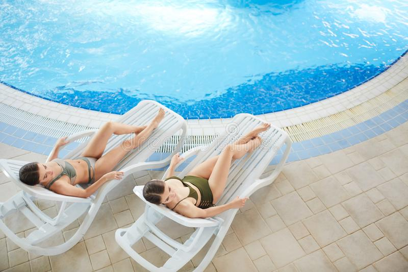 Beautiful Women Relaxing by Pool Above View stock photography