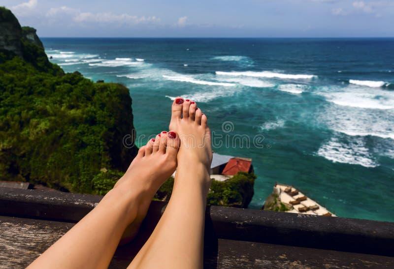 Beautiful women's feet on background of ocean royalty free stock photo
