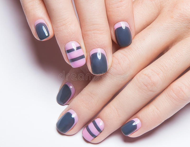 Beautiful women's manicure with gray and pink. Polish on the nails. Picture taken in the studio. Close-up stock photos