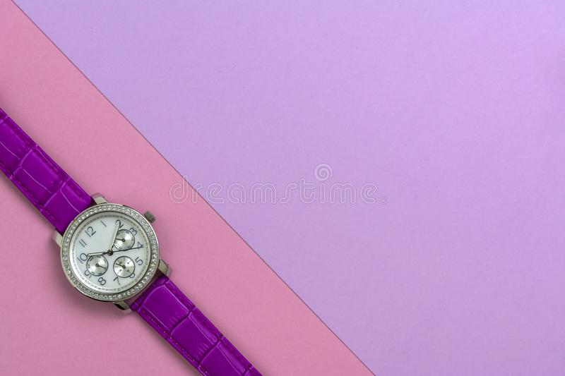 Beautiful women`s wrist watch on pink background royalty free stock images