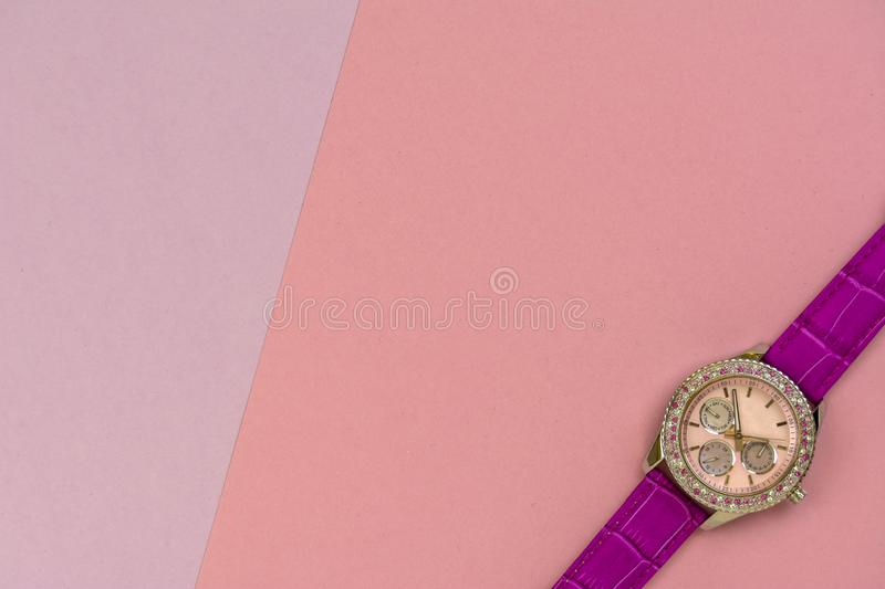 Beautiful women`s wrist watch on pink paper background stock photography