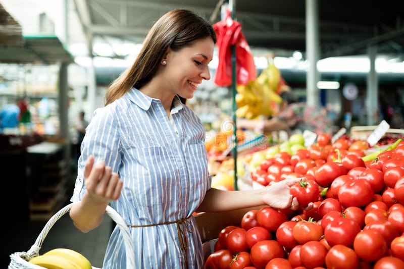 Beautiful happy young women shopping vegetables and fruits royalty free stock photography