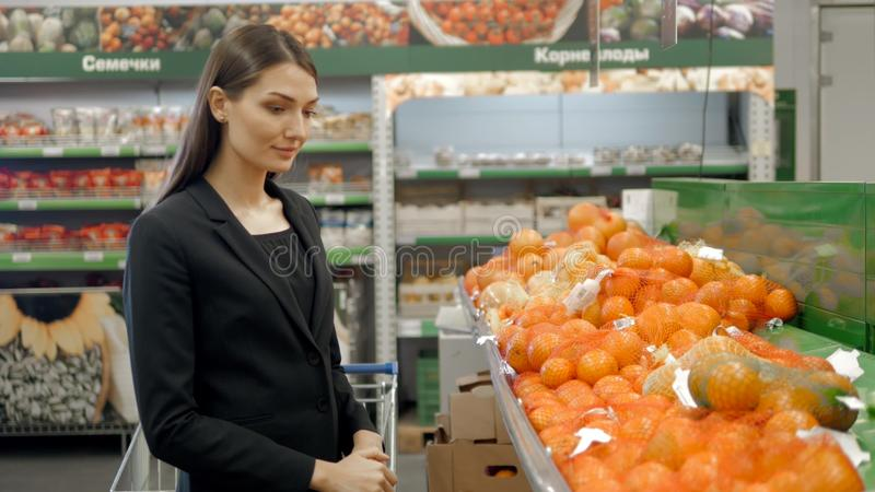 Beautiful women shopping vegetables and fruits in supermarket, brunette choose tomato and pepper, fresh salad stock images