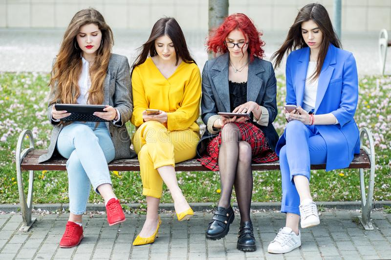 Beautiful women sit with gadgets on the bench. The concept of the Internet, social networks, study and lifestyle royalty free stock photography