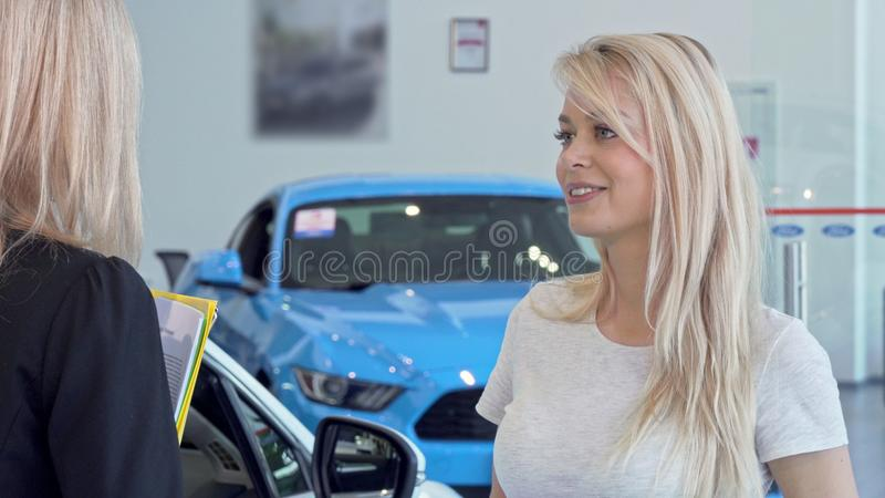 Beautiful woman talking to the salesperson at cars dealership salon. Beautiful women talking to the salesperson at cars dealership salon. Lovely cheerful female royalty free stock photos