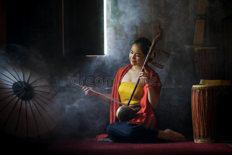 Beautiful women in traditional dress costume playing treble fiddle. Treble fiddle or soprano sounded string Thai music instrument royalty free stock photo