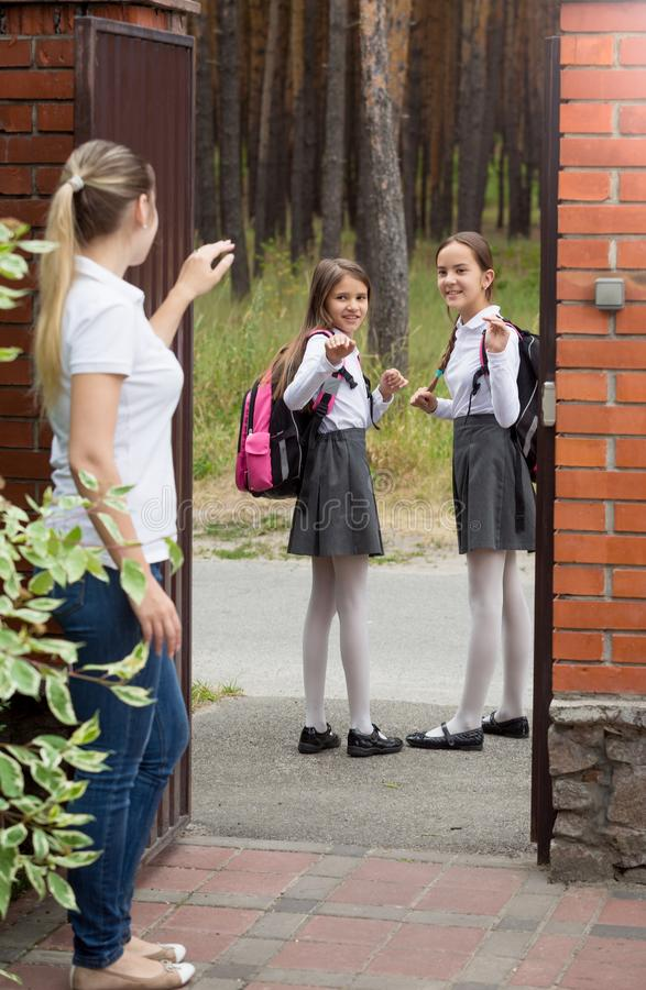 Young beautiful woman waving hands to her daughters leaving to school royalty free stock images