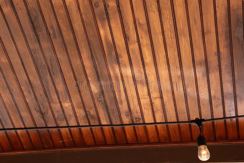 Beautiful Wood Slat Ceiling with Single Light Bulb. Gorgeous wood slats are featured in this beautiful celing with a single electrical cord hanging with a single royalty free stock photo