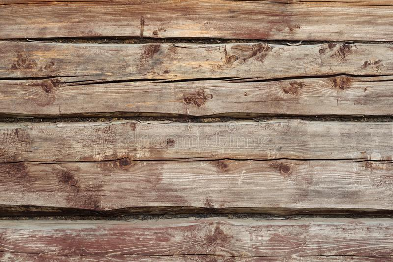 Beautiful wooden background from old weathered horizontal logs with knots and moss. view of the wal royalty free stock image