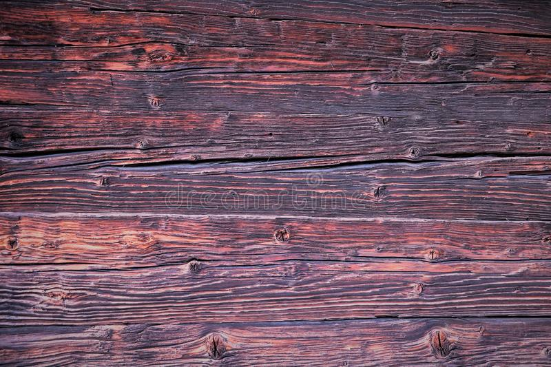 Background. Beautiful wooden boards, the wall of a wooden antique house in brown, red and pink tones. royalty free stock image