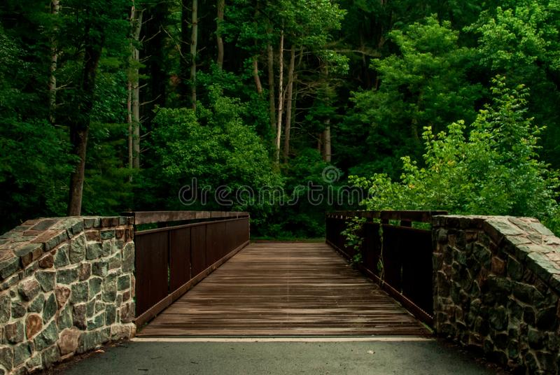 Wooden bridge with cobblestone foundation. Beautiful wooden bridge hidden inside park with a lush background and cobblestone pillars stock images