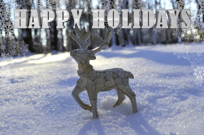 A beautiful wooden Christmas deer is standing in the snow with the inscription HAPPY HOLIDAYS royalty free stock photography