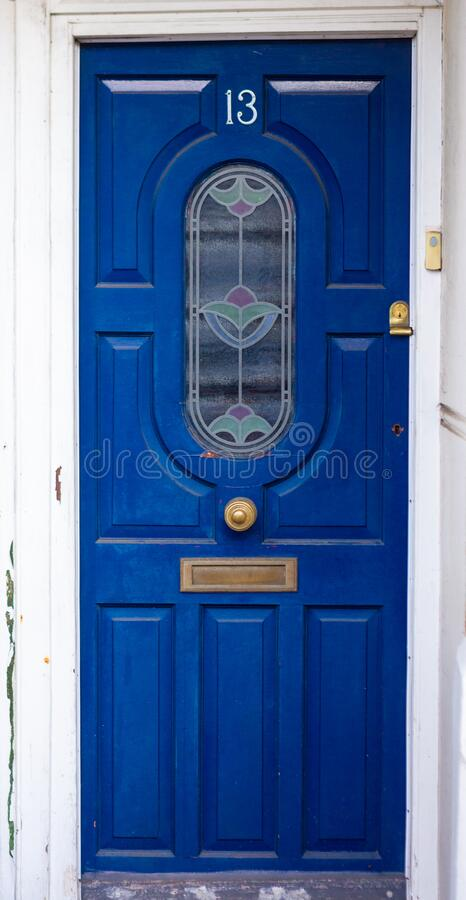 Beautiful wooden front door with stained glass. Lucky house number 13 on a blue wooden front door stock photography