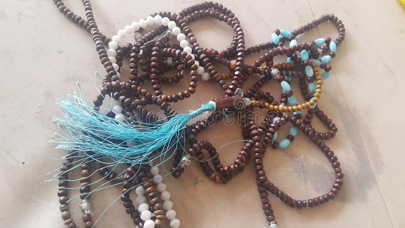 Beautiful wooden prayer beads or rosary placed over fabric background. Religion concept of ramadan or Eid for muslims religious faith necklace jewelry  islam stock photo