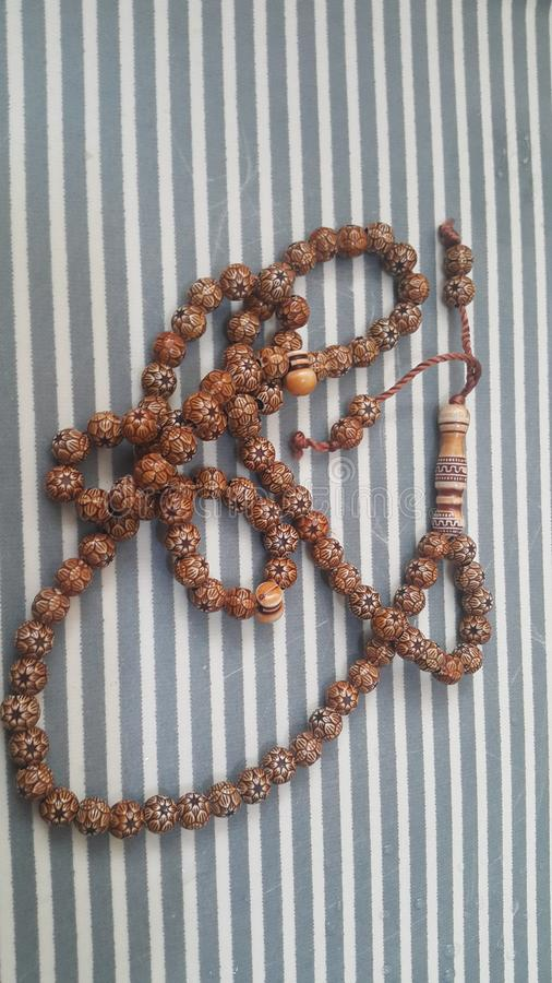 Beautiful wooden prayer beads or rosary with a striped background. Religion concept of ramadan or Eid for muslims religious faith necklace jewelry isolated stock photo