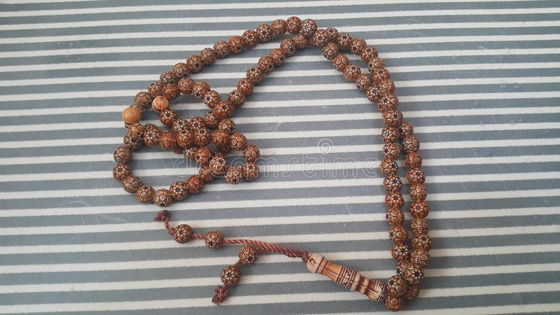 Beautiful wooden prayer beads or rosary with a striped background. Religion concept of ramadan or Eid for muslims religious faith necklace jewelry  islam royalty free stock images