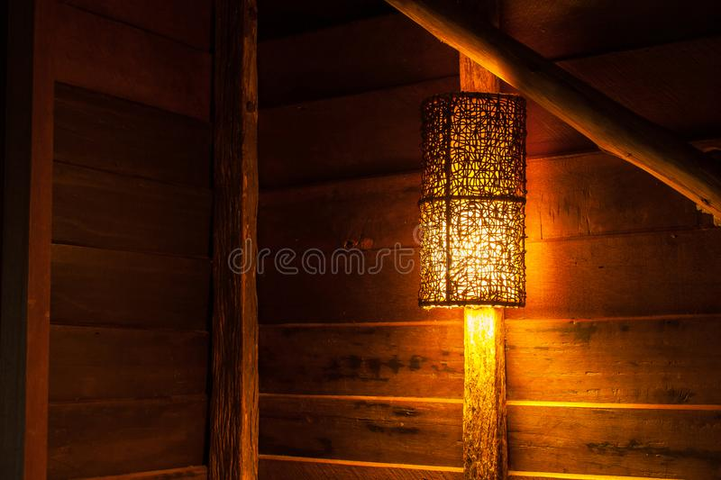 Beautiful wooden wall lamp hanging on wood log over the bed in the cottage at countryside. stock photo