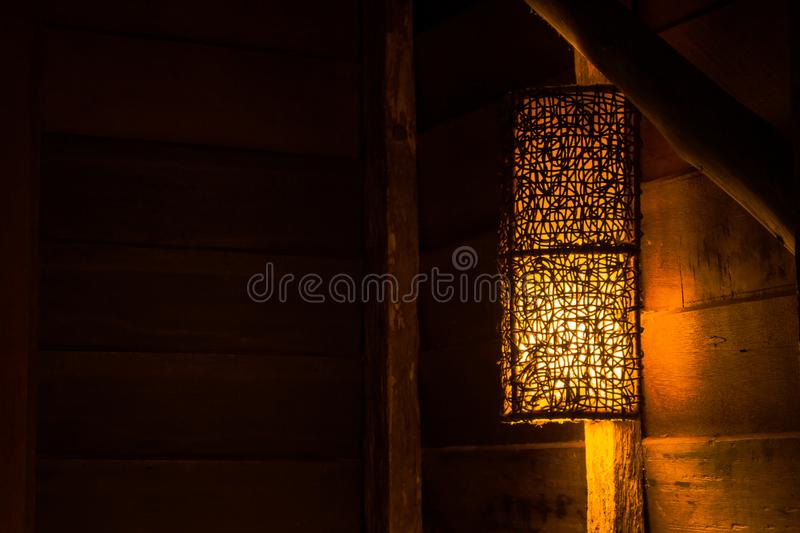 Beautiful wooden wall lamp hanging on wood log over the bed in the cottage at countryside. Selective focus royalty free stock images