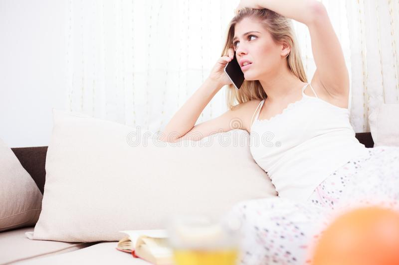Beautiful worried young woman talking on the phone royalty free stock photo