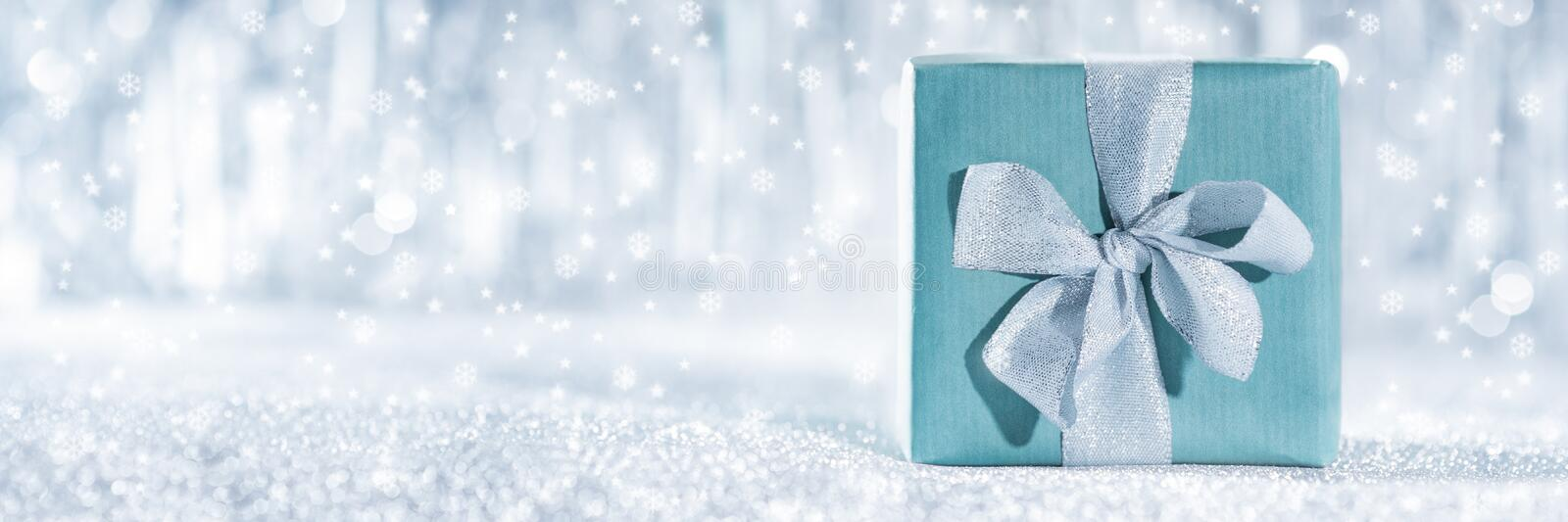 Beautiful wrapped christmas gift with defocused christmas lights in the background. Christmas banner. Beautiful wrapped christmas gift with defocused christmas royalty free stock images