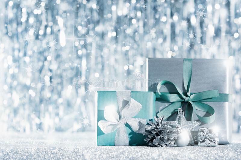 Beautiful wrapped christmas gifts and ornaments with defocused christmas lights in the background. Christmas backdrop. Beautiful wrapped christmas gifts and stock photos